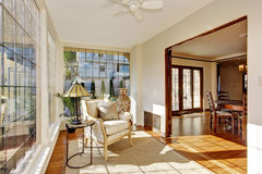 Bright sunroom with antique chair. Bright sunroom in soft ivory with antique chair and and small table stock images