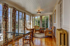 Bright sunroom with wicker furniture. Bright sunroom with french windows. Furnished with wicker table and chairs and glass top table stock images