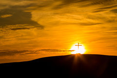 Bright Sunset Cross. Cross on a hill with a bright sun setting behind  it Royalty Free Stock Photography