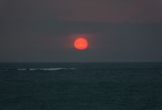 Bright sunset with large red sun under the ocean surface. And wave foam Stock Image