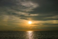 Bright sunset with large yellow sun under the sea surface. Sunset over sea landscape. Beautiful sunset with sky over calm sea in tropical island royalty free stock photo