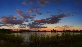 A bright sunset in the night sky. The landscape with the river stock photography