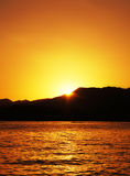 Bright sunset over the sea. And over mountains Royalty Free Stock Photography
