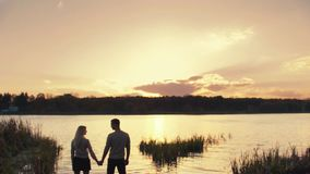 Bright sunset by the riverside, amazing sky, the silhouette of the young couple holding their hands, looking at each stock video