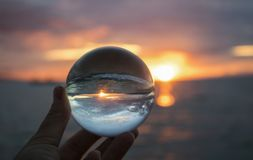 Bright Sunset Seascape with Boat on Horizon Captured in Glass Ba. Sunset on horizon over ocean with wave breaking on sand captured in glass ball royalty free stock image