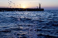 Bright sunset under the sea and pier with waves splashes. Stock Photo