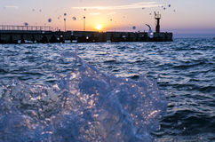 Bright sunset under the sea and pier with waves splashes. Royalty Free Stock Photos