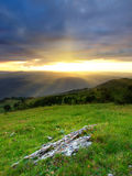 Bright sunshine and hill. The bright sunshine during the sunset. Green meadow and the hills Stock Images