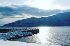 Bright sunshine over winter lake with dock. Winter landscape scene with sun behind clouds over mountain and lake. Sunshine reflecting on water next to dock. Snow Stock Image