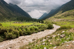 Bright sunshine before the storm illuminates powerful river in a valley in mountains Stock Photography