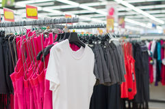 Bright t-shirts and shorts on stands Royalty Free Stock Image