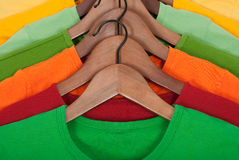 Bright t-shirts on wooden hangers Stock Photos