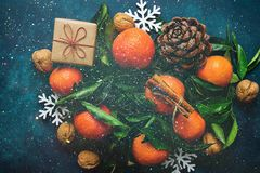 Bright Tangerines Green Leaves Pine Cones Gift Box Snow Flakes on Dark Blue Background.Sparkling Glitter Lights Christmas New Year Royalty Free Stock Photography