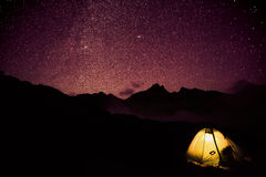 Bright tent in mountains and stars Stock Photo