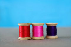 Bright Thread. Vintage wooden spools with bright colored thread, against a blue background Stock Images