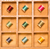 Bright thread on spools in shadow box Royalty Free Stock Photos