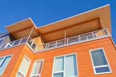 Bright timber clad condo building exterior detail. Upper storey detail of timber clad apartment building painted bright with penthouse balcony under blue sky Royalty Free Stock Photography