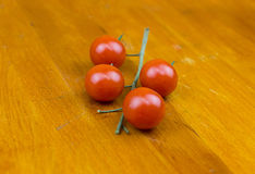 Bright tomatoes on a branch lies on a cutting wooden board Royalty Free Stock Photo