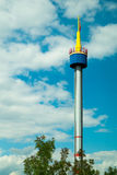 Bright tower against the blue sky with clouds Stock Photography