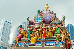 Bright Tradition vs Dull Modernity. The colourful roof of the Sri Mariamman Temple stands in bright contrast to the skyscrapers of Singapore Stock Images