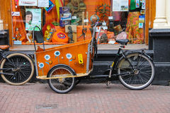 Bright tricycle with a big luggage basket on Kruisstraat street Stock Images