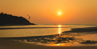 Bright tropical sunset at low tide in Goa, India Stock Image