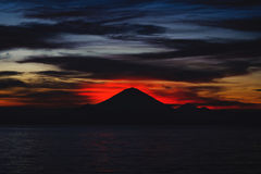 Bright tropical sunset and silhouettes of Agung volcano on the island of Bali in Indonesia. Magic colors during sunset, bright clouds and red sun light Stock Photo