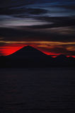 Bright tropical sunset and silhouettes of Agung volcano on the island of Bali in Indonesia. Magic colors during sunset, bright clouds and red sun light Stock Photos