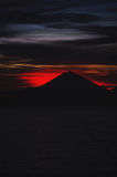 Bright tropical sunset and silhouettes of Agung volcano on the island of Bali in Indonesia. Magic colors during sunset, bright clouds and red sun light Royalty Free Stock Images