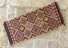 Bright Turkish carpets hanging on a stone wall stock photography