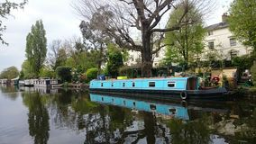 Bright turquoise river house boat Stock Photos