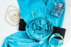 Bright turquoise women`s dress and accessories on a white background. Flower belt, pearl necklace, earrings, bracelet and perfume stock photo