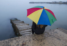 Bright umbrella with girl on misty day at beach Royalty Free Stock Image