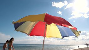 Bright umbrella stands on the beach. Protection from sunlight. People are walking along the beach. Summer season stock video
