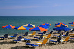 Bright Umbrellas on the Beach. Colorful umbrellas and chaise lounges on the beach on island Crete in Greece Royalty Free Stock Photo
