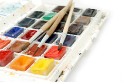 Bright used watercolor paints in box and  brushes isolated on a white background. Macro shot. Stock Images