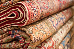 Bright various oriental rugs and carpets stacked for display. Stock Photo