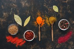 Bright various spices, wooden spoons on a dark rustic background. View from above. Bright various spices, wooden spoons on a dark rustic background. View from Stock Images
