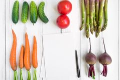Bright vegetables and a cookbook on white background. Healthy food for salad. Flat lay, top view, view from above stock photo
