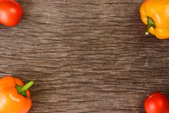 Bright vegetables and fruits yellow and orange peppers, red tomatoes, yellow lemon, green dill. Against the background of an old cracked sun-bleached board royalty free stock photography