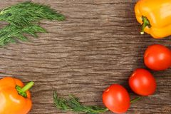 Bright vegetables and fruits yellow and orange peppers, red tomatoes, yellow lemon, green dill. Against the background of an old cracked sun-bleached board stock photos
