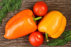 Bright vegetables and fruits yellow and orange peppers, red tomatoes, yellow lemon, green dill. Against the background of an old cracked sun-bleached board stock images