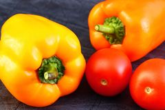 Bright vegetables and fruits yellow and orange peppers, red tomatoes, yellow lemon, green dill. Against the background of an old cracked sun-bleached board stock image
