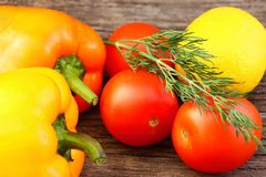 Bright vegetables and fruits yellow and orange peppers, red tomatoes, yellow lemon, green dill. Against the background of an old cracked sun-bleached board royalty free stock photo