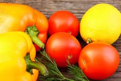 Bright vegetables and fruits yellow and orange peppers, red tomatoes, yellow lemon, green dill. Against the background of an old cracked sun-bleached board stock photo
