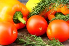 Bright vegetables and fruits yellow and orange peppers, red tomatoes, yellow lemon, green dill. Against the background of an old cracked sun-bleached board royalty free stock photos