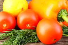 Bright vegetables and fruits yellow and orange peppers, red tomatoes, yellow lemon, green dill. Against the background of an old cracked sun-bleached board royalty free stock image