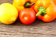 Bright vegetables and fruits yellow and orange peppers, red tomatoes, yellow lemon, green dill. Against the background of an old cracked sun-bleached board stock photography