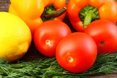 Bright vegetables and fruits yellow and orange peppers, red tomatoes, yellow lemon, green dill. Against the background of an old cracked sun-bleached board royalty free stock images