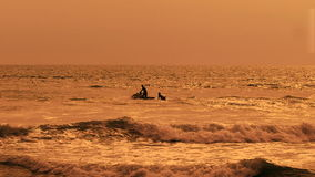 Bright view of wave runner cutting up the ocean with two men on it. Picture of Balinese sunset with brown water and sky stock video footage